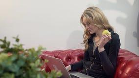 Härlig ung blond kvinna på den röda soffan genom att använda bärbara datorn och äta ett grönt äpple i vardagsrum royaltyfri bild