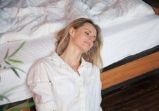 Härlig ung blond kvinna på sängen hemma arkivbild