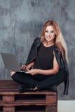 Härlig ung blond kvinna som använder den bärbara bärbar datordatoren, medan sitta i ett tappningställe le deltagare för kvinnlig Arkivbilder
