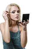 Härlig ung blond kvinna som gör makeup Arkivfoton