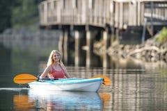Härlig ung blond kvinna som kayaking på sjön Arkivbild
