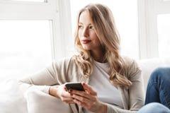Härlig ung blond kvinna som kopplar av på en soffa royaltyfria foton