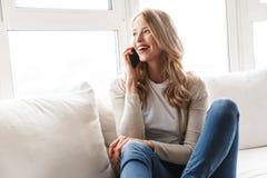 Härlig ung blond kvinna som kopplar av på en soffa fotografering för bildbyråer