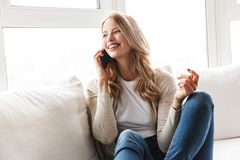 Härlig ung blond kvinna som kopplar av på en soffa royaltyfri fotografi