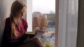 Härlig ung blond kvinna som läser en bok och sitter på fönsterbrädan lager videofilmer