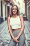 Härlig ung blond kvinna som ler i stads- bakgrund royaltyfri fotografi