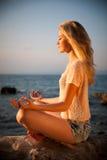 Härlig ung blond kvinna som mediterar på en strand på soluppgång in Royaltyfri Bild
