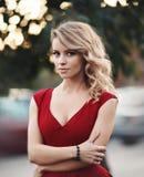 Härlig ung blond modell i en röd klänning som poserar på den oskarpa naturen Arkivfoton