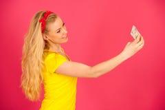 Härlig ung blond tonårs- kvinna i den gula t-skjortan som tar se Arkivfoton