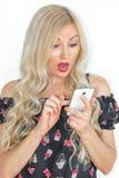 Härlig ung blondin med långt hår som ser förvånat på en mobiltelefon royaltyfria bilder