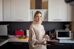 Härlig ung blondin som rymmer en stekpanna för att starta laga mat, själv-matlagning sund mat arkivbilder