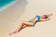 Härlig ung blondin som tycker om solen på den tropiska kusten Royaltyfri Fotografi