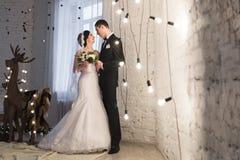 Härlig ung brud och brudgum som omfamnar i interien för nytt år Arkivfoton