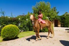 Härlig ung brunett med den röda klänningen och hennes brunt-blonda hors Royaltyfri Foto