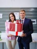 Härlig ung brunett och stilig man med en stor gåva för kollega äganderätt för home tangent för affärsidé som guld- ner skyen till Royaltyfri Foto