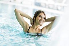 Härlig ung brunett som kopplar av i en simbassäng Arkivbild