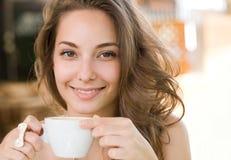 Härlig ung brunett som tycker om kaffe. Royaltyfria Foton
