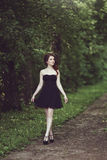Härlig ung brunettflicka i kort svart klänning som går till och med träna Royaltyfri Foto
