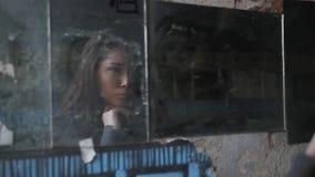 Härlig ung brunettflicka med långt hår som ser henne i brutna speglar på gatan arkivfilmer