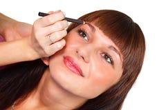 Härlig ung brunettflicka som gör makeup Arkivfoto