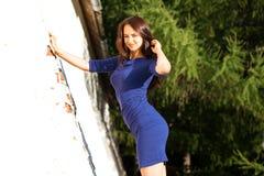 Härlig ung brunettkvinna i sexig blå klänning royaltyfri fotografi
