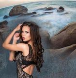 Härlig ung brunettkvinna mot stenig kust eller stranden Arkivfoton