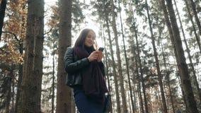 Härlig ung brunettkvinna som använder Smartphone i Autumn Park Flicka som går i Forest In Fall, livsstilbegrepp Royaltyfri Fotografi