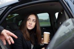 Härlig ung brunettkvinna som går att få ut ur bilen royaltyfri foto