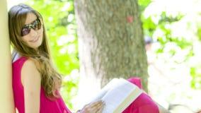 Härlig ung brunettkvinna som läser en bok lager videofilmer