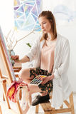 Härlig ung caucasian dammålare på workspace Royaltyfri Fotografi