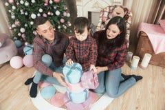 Härlig ung caucasian familj med gåvaaskar nära jul royaltyfri fotografi