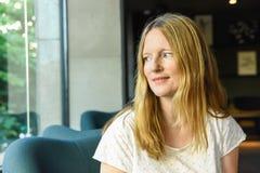 Härlig ung caucasian kvinna med ögon för blont hår för långa som blåa sitter i den europeiska amerikanska kafévardagsrummet som s arkivfoto