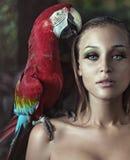 Härlig ung dam med en papegoja på en skuldra Arkivfoton