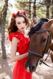 Härlig ung dam som bär den röda klänningen som rider en häst på den soliga sommardagen Brunett med långt lockigt hår med blommor  Royaltyfri Foto