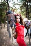 Härlig ung dam som bär den röda klänningen som rider en häst på den soliga sommardagen Brunett med långt lockigt hår med blommor  Royaltyfri Bild