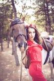 Härlig ung dam som bär den röda klänningen som rider en häst på den soliga sommardagen Brunett med långt lockigt hår med blommor  Royaltyfri Fotografi