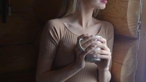 Härlig ung eftertänksam kvinnainnehavkopp av varmt te och anseende vid fönstret Royaltyfria Foton