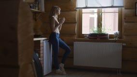 Härlig ung eftertänksam kvinnainnehavkopp av varmt te och anseende vid fönstret Arkivbilder
