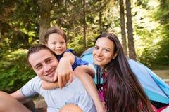 Härlig ung familj med dottern som campar i skog Arkivbilder