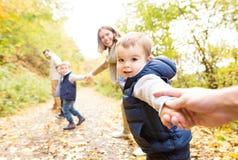 Härlig ung familj på en gå i höstskog Royaltyfri Bild
