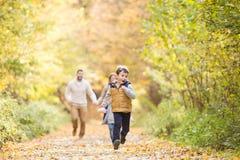 Härlig ung familj på en gå i höstskog Arkivfoton