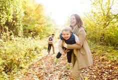 Härlig ung familj på en gå i höstskog Arkivbilder