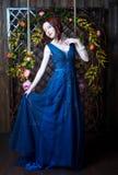 Härlig ung flicka i aftonklänningen som poserar på inre foto s Arkivfoton