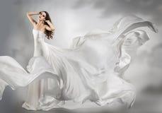 Härlig ung flicka i den vita klänningen för flyg royaltyfria foton