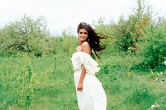 Härlig ung flicka i den vita klänningen i våren som blomstrar äpplefruktträdgårdar Arkivbild