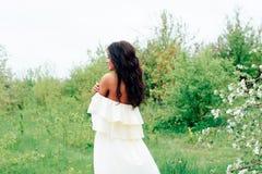 Härlig ung flicka i den vita klänningen i våren som blomstrar äpplefruktträdgårdar Royaltyfria Bilder