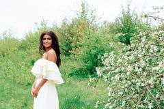 Härlig ung flicka i den vita klänningen i våren som blomstrar äpplefruktträdgårdar Arkivfoto