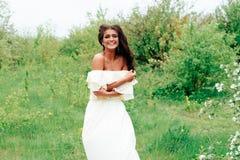 Härlig ung flicka i den vita klänningen i våren som blomstrar äpplefruktträdgårdar Arkivbilder