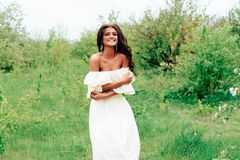 Härlig ung flicka i den vita klänningen i våren som blomstrar äpplefruktträdgårdar Royaltyfri Foto
