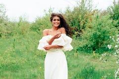 Härlig ung flicka i den vita klänningen i våren som blomstrar äpplefruktträdgårdar Royaltyfri Bild